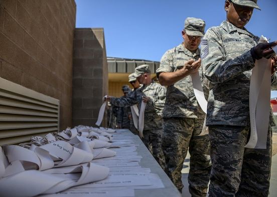 Airmen assigned to the 56th Fighter Wing pick up ribbons before a ten story stair climb Sept. 11, 2017 at Luke Air Force Base, Ariz. The Airmen climbed and descended ten stories of stairs in the air traffic control tower carrying ribbons that contained the names of those who lost their lives during the terrorist attack. (U.S. Air Force photo/Airman 1st Class Caleb Worpel)