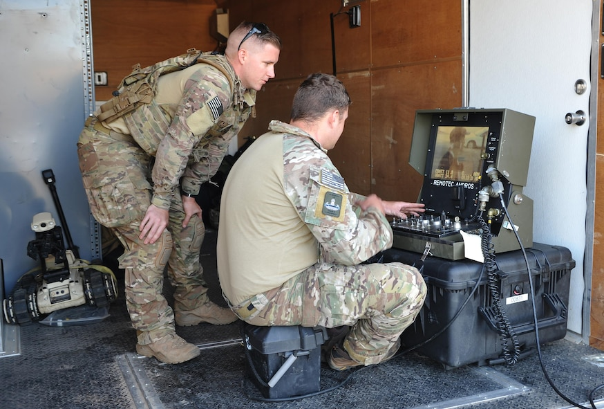 Senior Airman Jared Basham (left) and Staff Sgt. Robert Powell, 9th Civil Engineer Squadron explosive ordnance technicians, use a robot to remotely view a house during Urban Shield