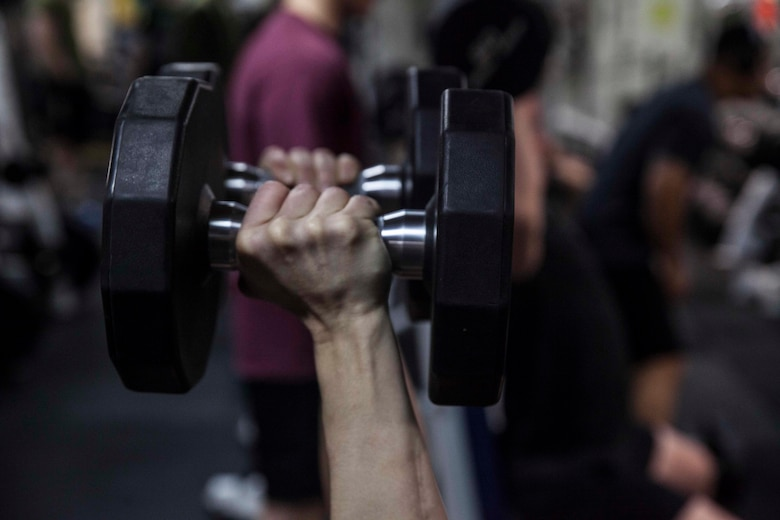 Staff Sgt. Cary Chase lifts a set of dumbbells during a workout in the gym aboard the USS Bonhomme Richard (LHD 6) while underway in the Pacific Ocean, Aug. 27, 2017.