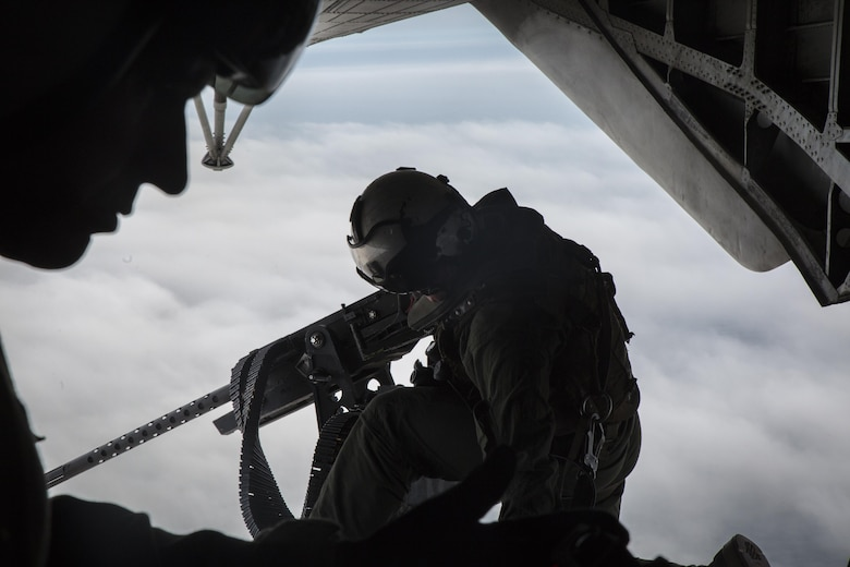 A crew chief adjust his gunner's belt from the back of a CH-53E Super Stallion above Draughon Range near Misawa Air Base, Japan, August 21, 2017, in support of exercise Northern Viper 17. This combined-joint exercise is held to enhance regional cooperation between participating nations to collectively deter security threats. The crew chief is assigned to Marine Heavy Helicopter Squadron 462, Marine Aircraft Group 16, 3rd Marine Aircraft Wing, currently forward deployed under the Unit Deployment Program with Marine Aircraft Group 36, 1st MAW, based out of Okinawa, Japan. (U.S. Marine Corps photo by Lance Cpl. Andy Martinez)