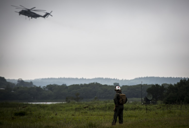 A U.S. Navy Corpsman observes a CH-53E Super Stallion at Draughon Range near Misawa Air Base, Japan, August 21, 2017, during external lift training in support of exercise Northern Viper 17. This combined-joint exercise is held to enhance regional cooperation between participating nations to collectively deter security threats. (U.S. Marine Corps photo by Lance Cpl. Andy Martinez)
