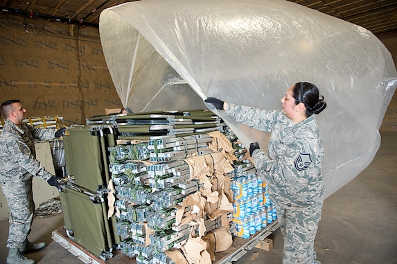 Master Sgt. Angie Hall, 434th Logistics readiness Squadron combat readiness technician, and Master Sgt. Adam Oswalt, 434th LRS training manager, place plastic sheeting on top of cargo at Grissom Air Reserve Base, Ind., Sept. 11, 2017. The pallet of cargo is being prepared for shipment to Florida as part of Hurricane Irma relief efforts. (U.S. Air Force photo/Douglas Hays)