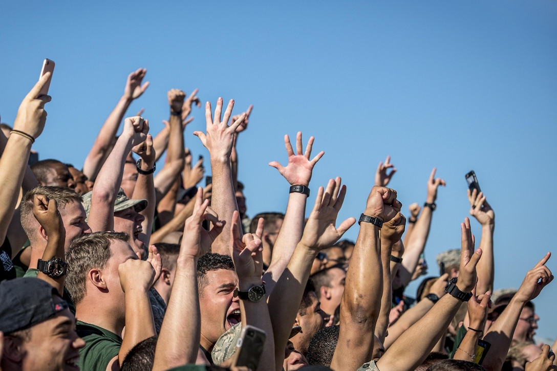 Airmen raise their hands to celebrate their win.
