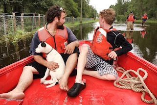 People and a dog sit in a boat, while members of the Coast Guard walk behind it in knee deep water.