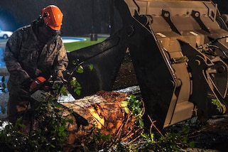 A member of the Air Force uses a chain saw to cut a tree trunk.