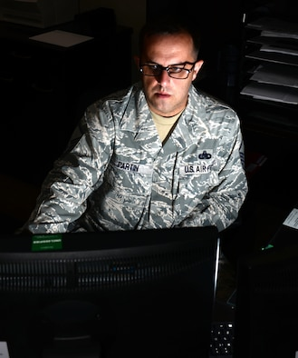Master Sgt. Leon Partin, the unit deployment manager assigned to the 28th Operations Support Squadron, checks emails on his computer Aug. 14, 2017, on Ellsworth Air Force Base, S.D. Squadron UDMs often stay after work to ensure that Airmen who are deploying have all the necessary equipment, training and paperwork. (U.S. Air Force photo by Airman 1st Class Thomas Karol)