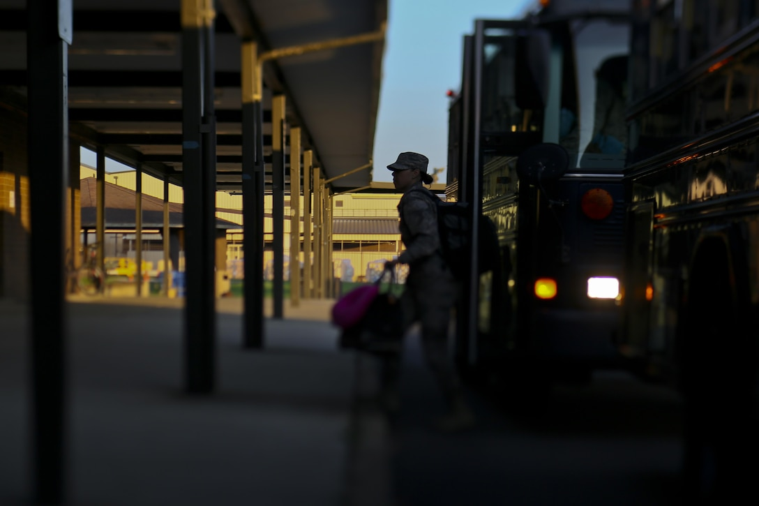 A U.S. Air Force airman from the New Jersey Air National Guard's 108th Wing departs a bus to enter the passenger terminal at Joint Base McGuire-Dix-Lakehurst, N.J., Aug. 20, 2017. The Guardsmen are deploying to Andersen Air Force Base, Guam. (U.S. Air National Guard photo by Master Sgt. Matt Hecht/Released)