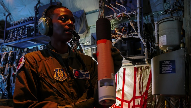 Air Force Reserve Tech. Sgt. Karen Moore, loadmaster, 53rd Weather Reconnaissance Squadron, Keesler Air Force Base, Mississippi, prepares a dropsonde to release into Hurricane Irma while flying into the hurricane, Sep. 8, 2017.
