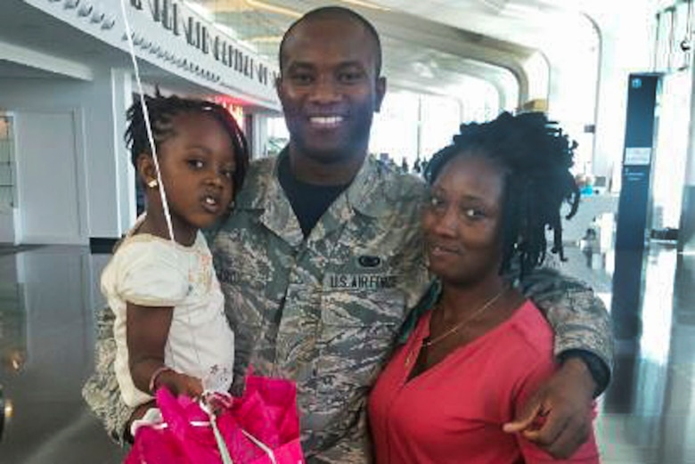 An airman, his wife and daughter pose for a photo at an airport.