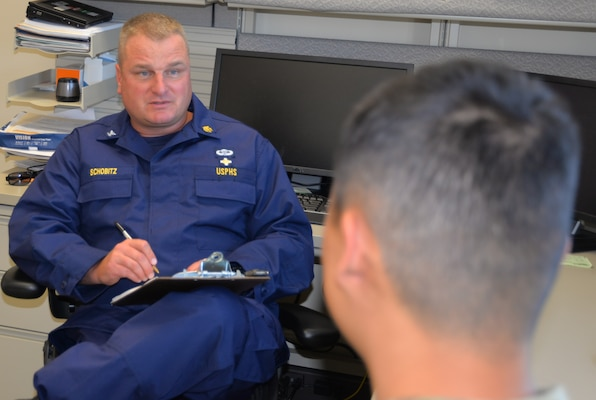 Capt. Richard Schobitz, chief of the Intensive Outpatient Behavioral Health Program and licensed clinical psychologist with the U.S. Public Health Service, talks to a Soldier in his office. The Intensive Outpatient Behavioral Health Program provides services and coping strategies to active duty members who have mental health issues, including anxiety, depression, post-traumatic stress disorder, or PTSD, and who have thoughts of committing suicide.