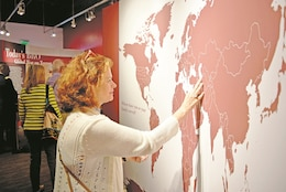 """Jane MacDougall, wife of Col. Mark MacDougall, chief of nursing officer at Irwin Army Community Hospital, places a sticker on every location where her family has been stationed as part of the exhibit """"Duty First: 100 Years of the Big Red One"""" at the Flint Hills Discovery Center in Manhattan, Kansas, Aug. 25."""