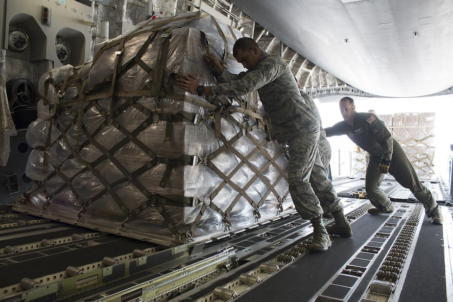 Tech. Sgt. Bryan Ulloa, 445th Force Support Squadron Services Flight services manager, helps Tech. Sgt. Andrew Wagner, 89th Airlift Squadron loadmaster, load cargo on board a 445th Airlift Wing C-17 Globemaster III Monday. Four Airmen from the 445th FSS flew with the cargo that included a pallet of meals ready to eat, a pallet of water and one ISU 90 loaded with cots bound for Homestead Air Reserve Base, Florida. (U.S. Air Force photo/Master Sgt. Patrick O'Reilly