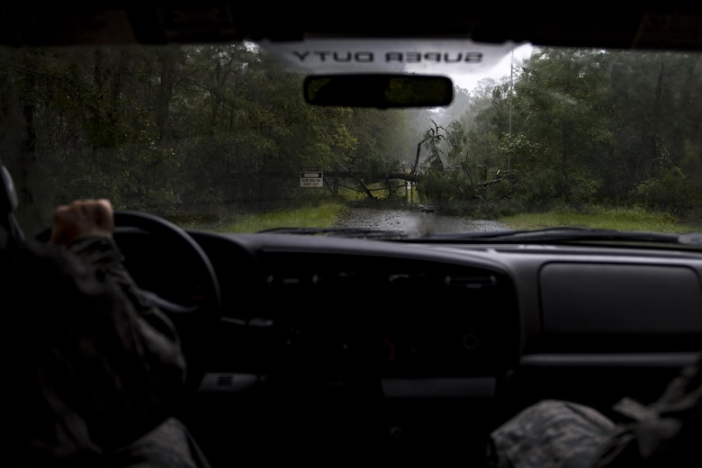 Members of Moody's ride-out team stop their vehicle in front of a fallen tree that blocks a road, Sept. 11, 2017, at Moody Air Force Base, Ga. Moody's ride-out team consisted of approximately 80 Airmen who were tasked with immediately responding to mission-inhibiting damage caused by Hurricane Irma. (U.S. Air Force photo by Airman 1st Class Daniel Snider)