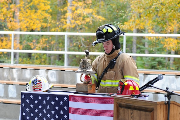 U.S. Air Force Airman 1st Class Justin Coker, a 354th Civil Engineer Squadron firefighter, rings a bell during a 9/11 Remembrance Ceremony, Sept. 11, 2017, at Eielson Air Force Base, Alaska. As part of fire fighter tradition a bell is rung in four sets of five rings to honor the fallen. (U.S. Air Force photo by Airman 1st Class Eric M. Fisher)