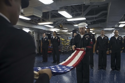 Petty Officer 1st Class Imre Balazsi folds the national ensign during a 9/11 remembrance ceremony aboard the multipurpose amphibious assault ship USS Bataan