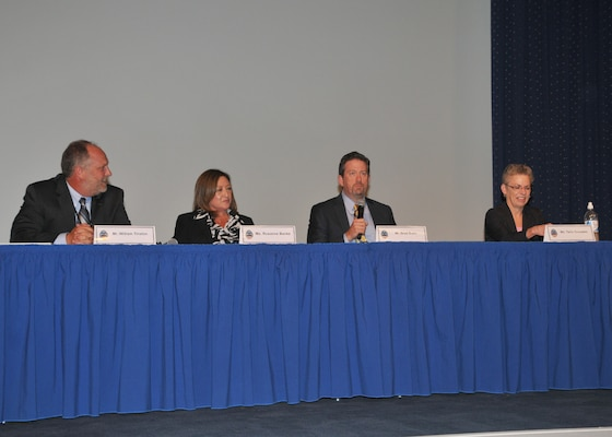 Panel, facing viewer, seated at table in business attire.