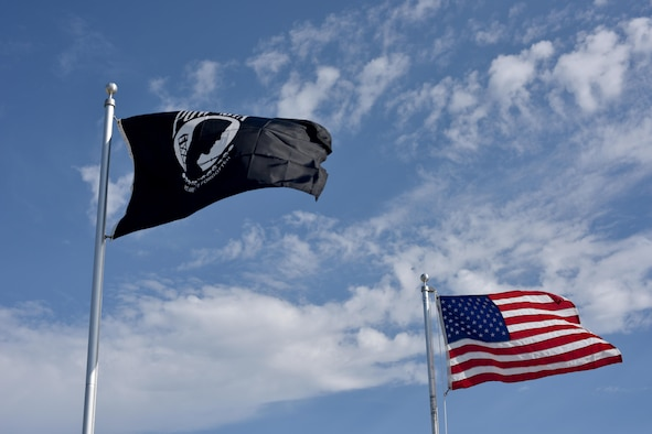 A Prisoners of War and Missing in Action  flag flies next to an American flag during the POW/MIA vigil at the parade field on Goodfellow Air Force Base, Texas, Sept. 8, 2017. Congress ordered prominent display of the POW/MIA flag on POW/MIA Recognition Day and several other national observances, including Armed Forces Day, Memorial Day, Flag Day, Independence Day and Veterans Day. (U.S. Air Force photo by Airman 1st Class Randall Moose/Released)