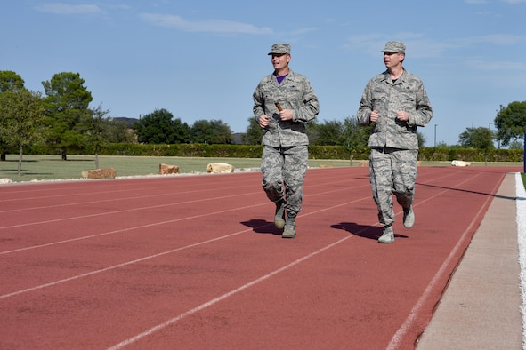 U.S. Air Force Col. Jeffrey Sorrell, 17th Training Wing vice commander, and Chief Master Sgt. Franklin Chism, 17th Mission Support Group superintendent, run during the Prisoners of War and Missing in Action Run at the track on Goodfellow Air Force Base, Texas, Sept. 8, 2017. Sorrell and Chism then began the run while carrying the POW/MIA baton. Participants would then take turns, passing the baton throughout the day. (U.S. Air Force photo by Airman 1st Class Randall Moose/Released)