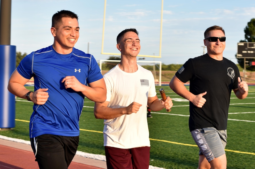 U.S. Air Force Maj. Mark Walkusky, 17th Communication Squadron commander, Airman 1st Class Nathaniel Singer, 17th CS transmissions systems operator, and Staff Sgt. Michael Janzen, 17th CS noncommissioned officer in charge, run during the Prisoners of War and Missing in Action Vigil at the track on Goodfellow Air Force Base, Texas, Sept. 8, 2017. In 1979, Congress proclaimed the first National POW/MIA Recognition Day to symbolize the steadfast resolve of the American people to never forget the men and women who gave up their freedom protecting theirs. (U.S. Air Force photo by Airman 1st Class Randall Moose/Released)