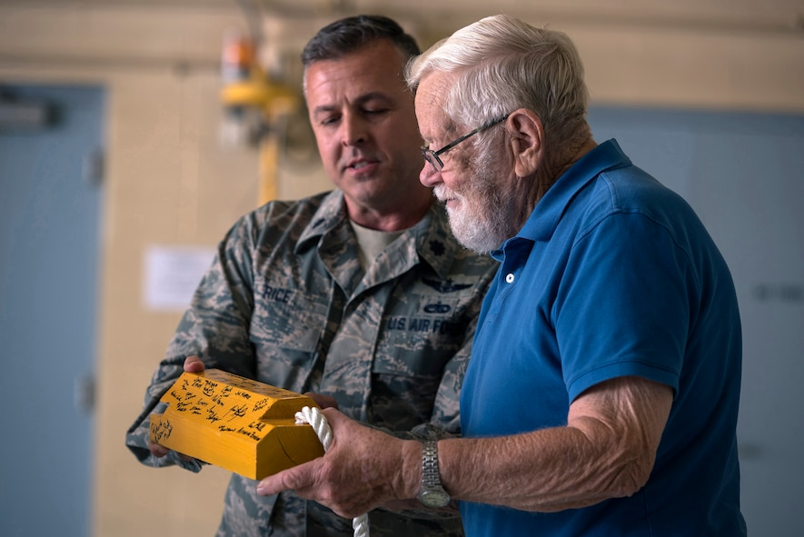 U.S. Air Force Lt. Col. Steven Rice, the deputy commander of the 182nd Maintenance Group, gives retired U.S. Air Force Chief Master Sgt. Homer Wells, a former chief of maintenance with the 182nd Tactical Air Support Group, an aircraft chock signed by the group during a ceremony honoring his service in Peoria, Ill., Aug. 24, 2017. Wells enlisted in 1947 and retired in 1984 with 37 years of service with the Illinois Air National Guard. (U.S. Air National Guard photo by Tech. Sgt. Lealan Buehrer)