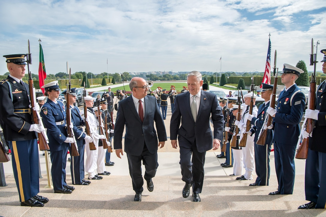 Defense Secretary Jim Mattis walks up the steps with the Portuguese defense minister.