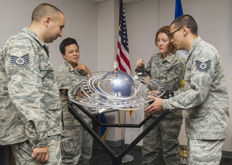 Members of the 310th Operations Support Squadron discuss the tracking of satellites orbiting the earth using a training aid on Saturday, Sep. 9th, 2017.