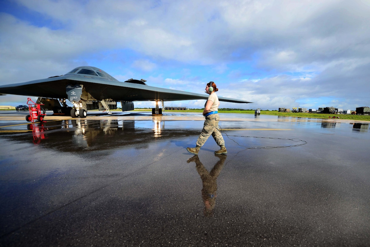 An airman walks toward an aircraft on a flightline.