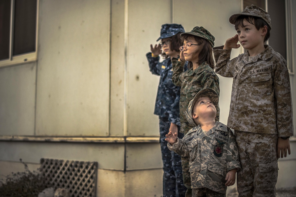 Four children in military uniforms stand and salute during a ceremony.