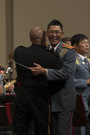 GINOWAN CITY, OKINAWA, Japan – U.S. Marine Chief Warrant Officer Andres Navarro, left, embraces Japan Ground Self-Defense Force 1st Lt. Toshiyuki Ishimura during the 22nd Annual Combined Band Concert Sept. 9 at the Ginowan Civic Hall in Ginowan City, Okinawa, Japan.