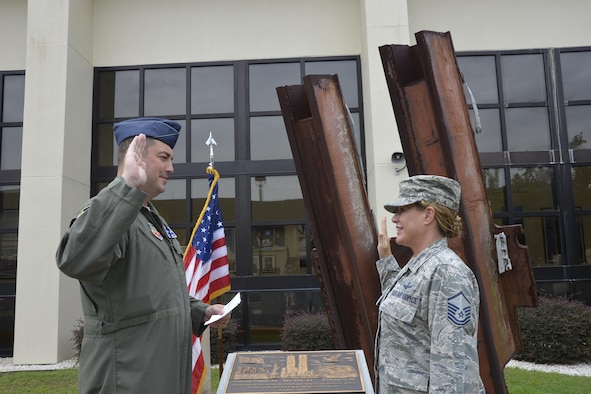 Lt. Col. Brian Lukowski, Director, Space Forces, Continental Aerospace Defense Region-1st Air Force (Air Forces Northern), issues the reenlistment oath to Master Sgt. Jamie Jo Walker, U.S. Air Force Space Command training manager, in front of the 9-11 Memorial at the 601st Air Operations Center, Tyndall Air Force Base, Fla. Walker is deployed from Air Force Space Command Headquarters, Peterson Air Force Base, Colo., to help support contingency operations for Hurricanes Harvey and Irma. (Photo by Mary McHale)