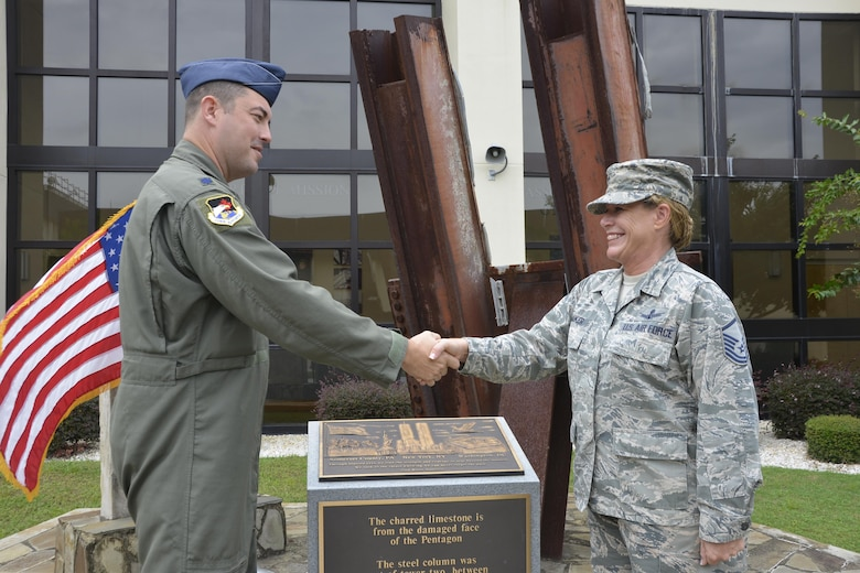 Lt. Col. Brian Lukowski, Director, Space Forces, Continental Aerospace Defense Region-1st Air Force (Air Forces Northern), congratulates Master Sgt. Jamie Jo Walker, U.S. Air Force Space Command training manager, following her taking the oath of reenlistment in front of the 9-11 Memorial at the 601st Air Operations Center, Tyndall Air Force Base, Fla. (Photo by Mary McHale)