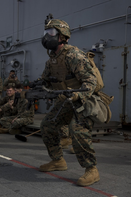 Lance Cpl. Benjamin Cartwright, an unmanned aerial system controller with Kilo Company, Battalion Landing Team, 3rd Battalion, 5th Marines, squats with an M240B medium machine gun during combat conditioning marksmanship training on the flight deck of the USS Bonhomme Richard (LHD 6) in the Pacific Ocean, June 24, 2017.