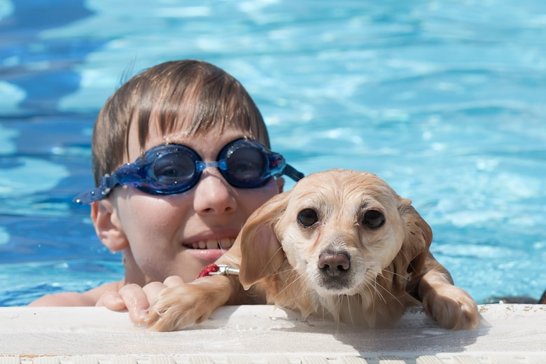 A dog rests the edge of the pool with its owner during the Dog Days of Summer event at Yokota Air Base, Japan, Sept. 9, 2017.