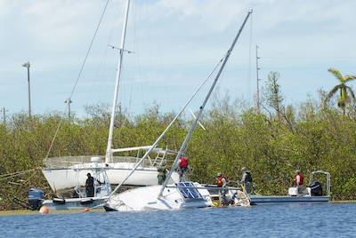 Teams with the Florida National Guard's Chemical Biological Radiological Nuclear Emergency Response Force-Package and the Florida Fish and Wildlife Conservation Commission search a demolished sailboat.