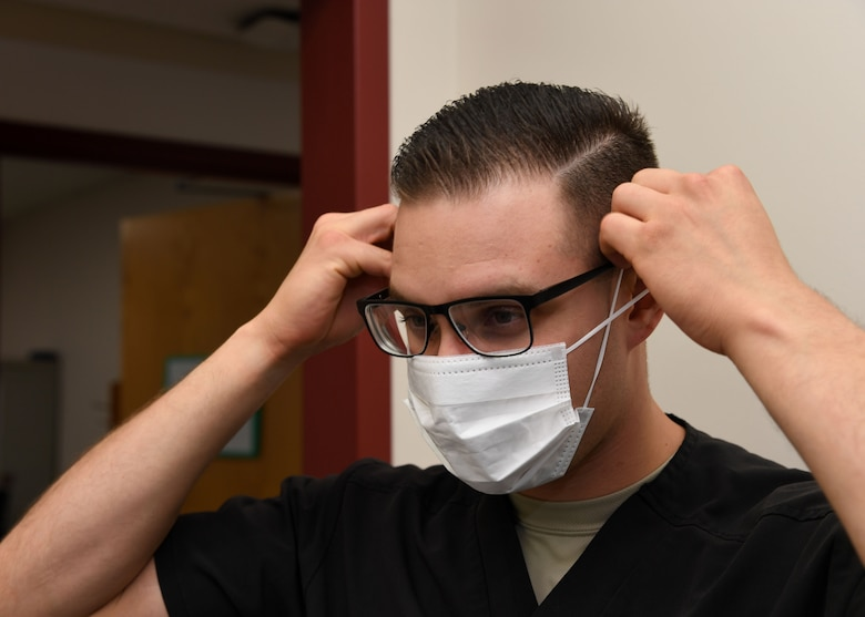 Senior Airman Alexis Lopez, dental assistant with the 319th Medical Group, demonstrates proper sanitary procedure by putting on a face mask Sept. 7, 2017, at the medical treatment facility on Grand Forks Air Force Base, N.D. Lopez said in addition to personal sanitation, there are also multiple steps taken to ensure treatment rooms are sanitary and prepared for patient use.