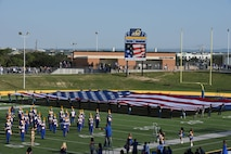 Angelo State University ROTC students unfold the American flag during the opening ceremonies of the Military Appreciation Day at LeGrand Stadium in San Angelo, Texas, Sept. 9, 2017. Along with the ceremonial unfolding of the flag the ROTC students also celebrated each touchdown with a run to the end zone and pushups. (U.S. Air Force photo by Airman Zachary Chapman/Released)