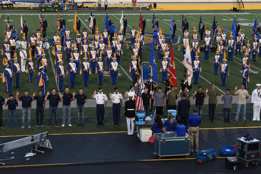 During halftime of the Military Appreciation Day game, approximately 50 delayed enlistment program individuals take the Oath of Enlistment at Angelo State University's LeGrand in San Angelo Tex. Sept. 9, 2017. U.S. Air Force Col. Ricky Mills, 17th Training Wing commander, administered the oath to future Soldiers, Sailors, Airmen and Marines. (U.S. Air Force photo by Airman Zachary Chapman/Released)