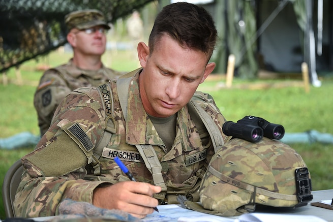 A soldier reads a map while seated at a table.