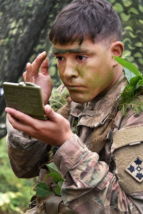 A soldier applies camouflage face paint before participating in the Expert Infantryman Badge competition.