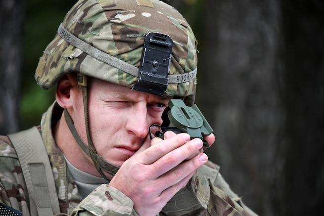 A soldier practices with a lensatic compass before participating in the Expert Infantryman Badge competition.