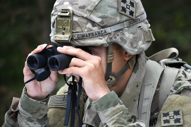 A soldier uses binoculars to locate his next objective participating in the Expert Infantryman Badge competition.