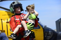 Coast Guard Petty Officer 3rd Class Evan Gallant, a rescue swimmer from Air Station Miami, carries a boy away from an MH-60 Jayhawk helicopter in Beaumont, Texas, Aug. 31, 2017. An aircraft crew working out of Air Station Houston transported a group of people from a shelter to Jack Brooks Regional Airport in Beaumont, Texas. (U.S. Coast Guard photo by Petty Officer 3rd Class Corinne Zilnicki/Released)