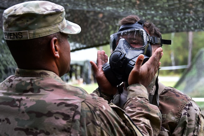 A soldier helps another with testing a gas mask during the Expert Infantryman Badge competition