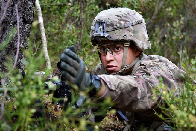 A soldier points his squad in the direction toward their next objective during the Expert Infantryman Badge competition