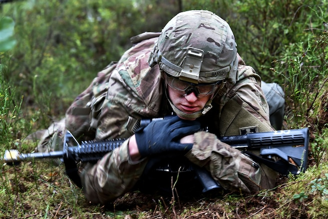 A soldier does a low crawl to the next station during the Expert Infantryman Badge competition.