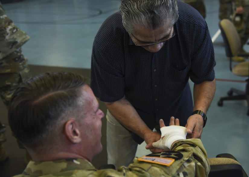 """Jacob """"Stitch"""" Duran, professional cutman, wraps the hand of U.S. Army Maj. Gen. Malcolm Frost, Initial Military Training commanding general, with his famous """"knock out"""" wrap at Joint Base Langley-Eustis, Va., Sep. 7, 2017."""
