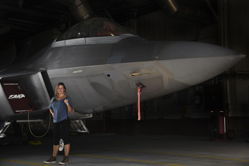 Miesha Tate, retired Ultimate Fighting Championship Bantamweight division champion, poses in front of an F-22 Raptor during a tour of Joint Base Langley-Eustis, Va., Sep. 8, 2017.