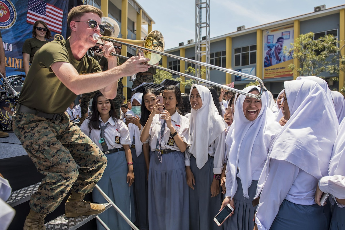 A Marine plays the trombone to smiling students in Indonesia.