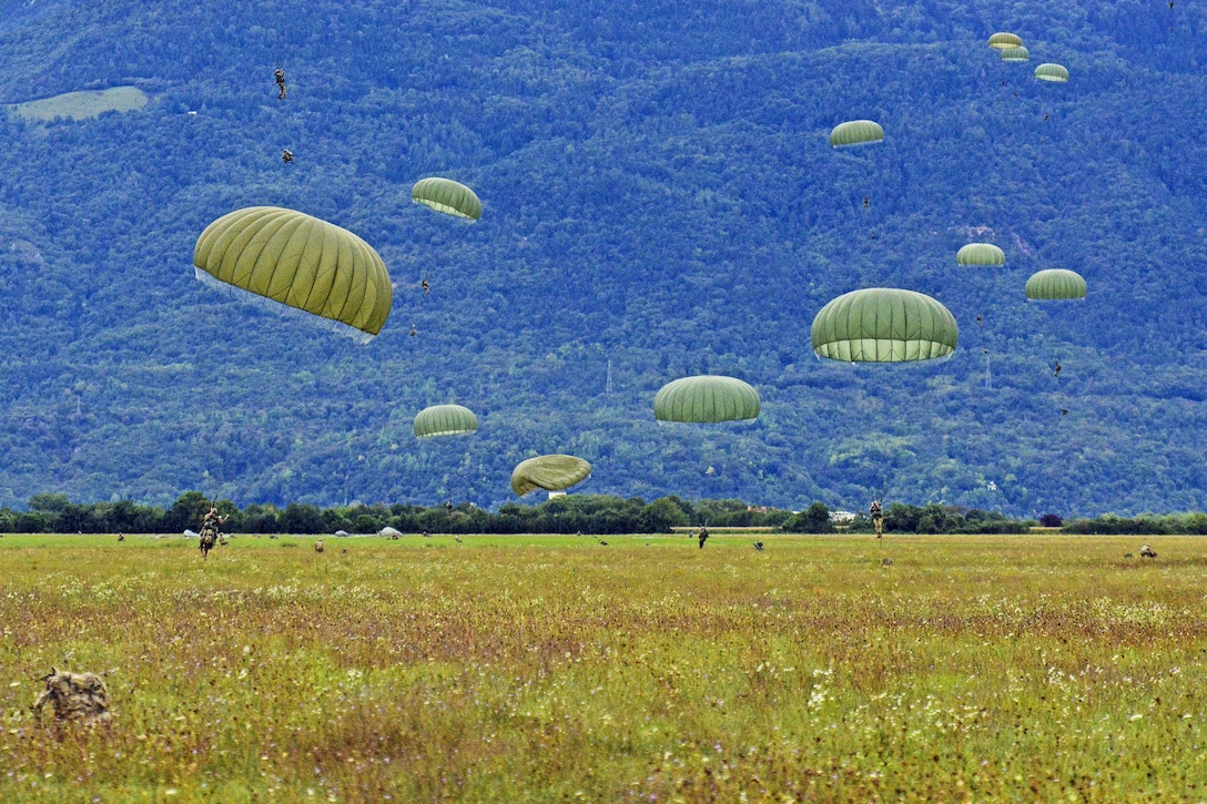 Soldiers with green parachutes land on green grass in front of a blue hill.
