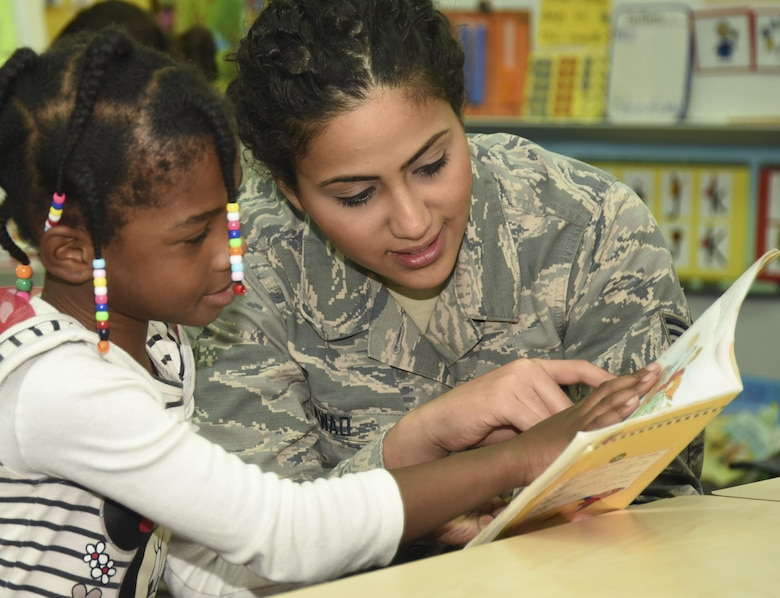 Senior Airman Sandra Awad, 301st Medical Squadron surgical technician, interacts with a special needs student while reading a book together Aug.23, 2017, at Lone Star Elementary School in Keller, Texas. Eight Reserve medical Airmen visited the school to connect and read to students as part their unit's community outreach program. (U.S. Air Force photo by Ms. Julie Briden-Garcia)